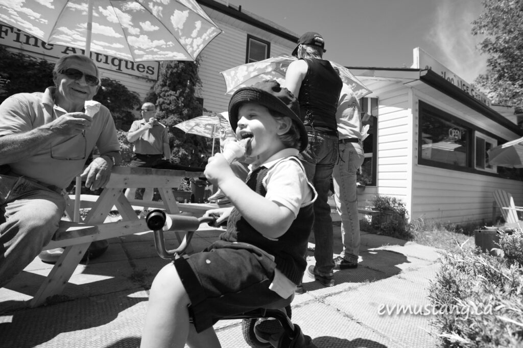 image of boy on tricycle eating ice cream in the sun