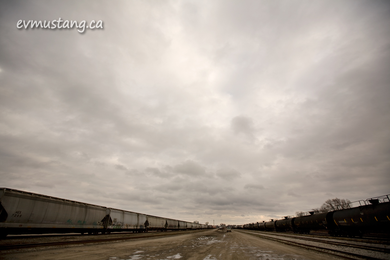 image of a train yard under a cloudy sky