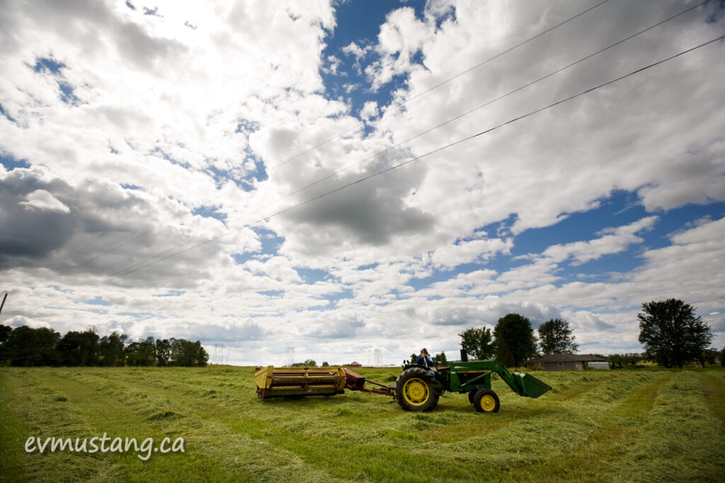 image of farmer mowing the first crop of hay under a warm summer sky