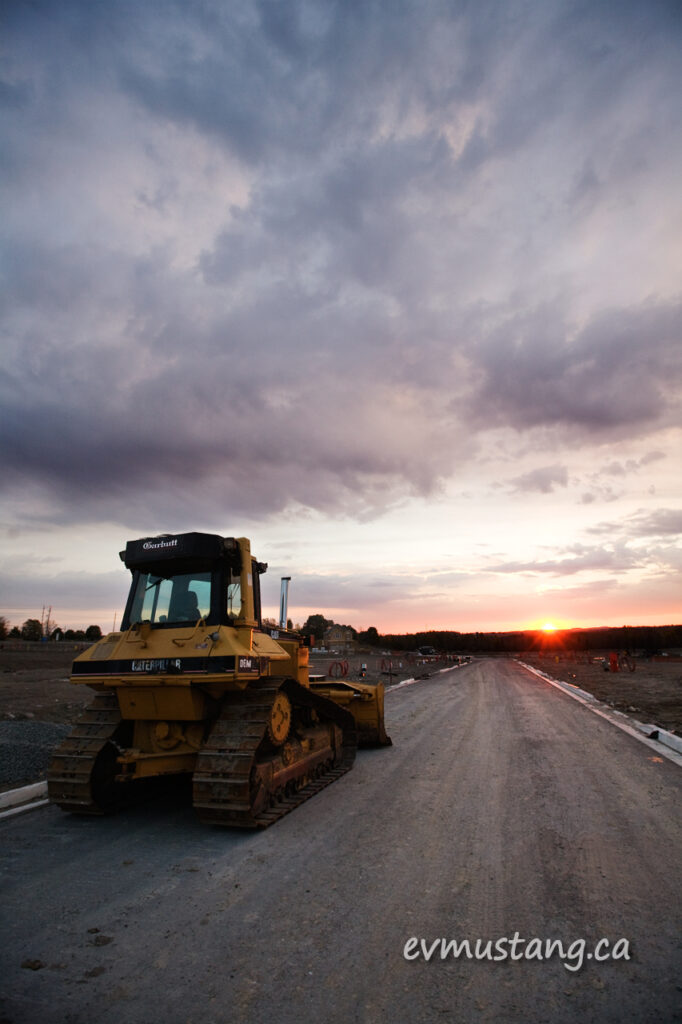 image of bulldozer in new subdivision with sunset