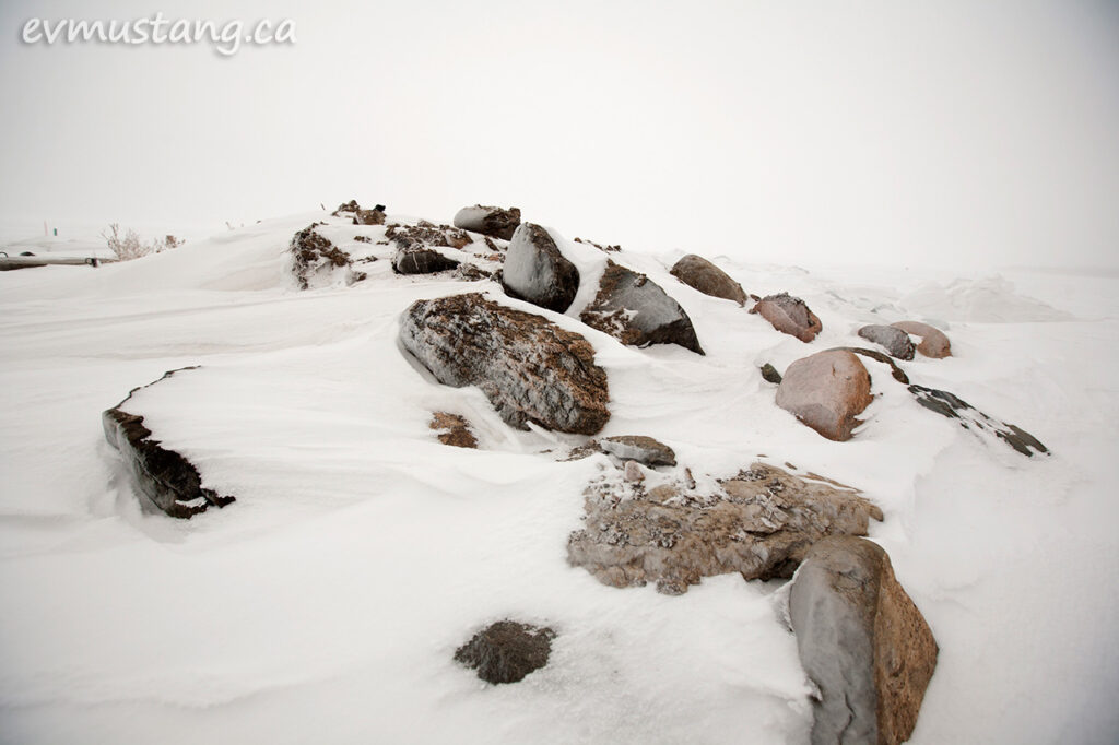 image of granite boulders in bleak snow beside a winter lake