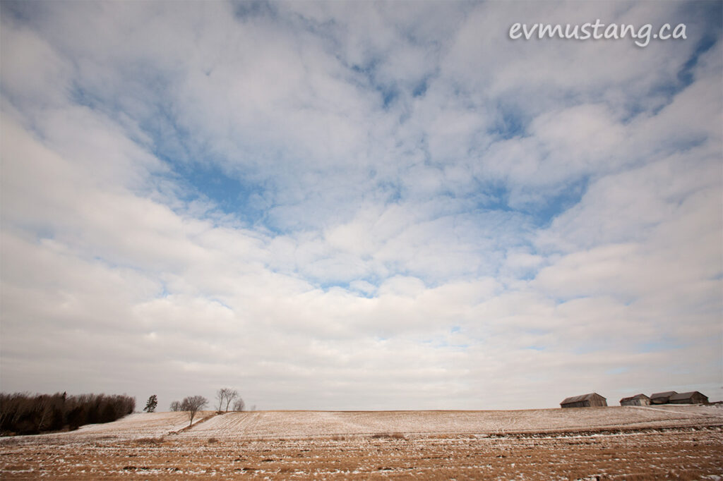 image of textured white clouds with blue sky over rust gold late winter field with sparse snow and barns in the distance