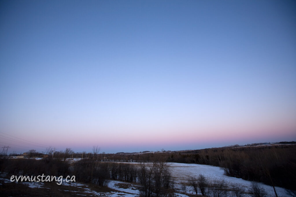 image of country field with light snow and soft coloured sky