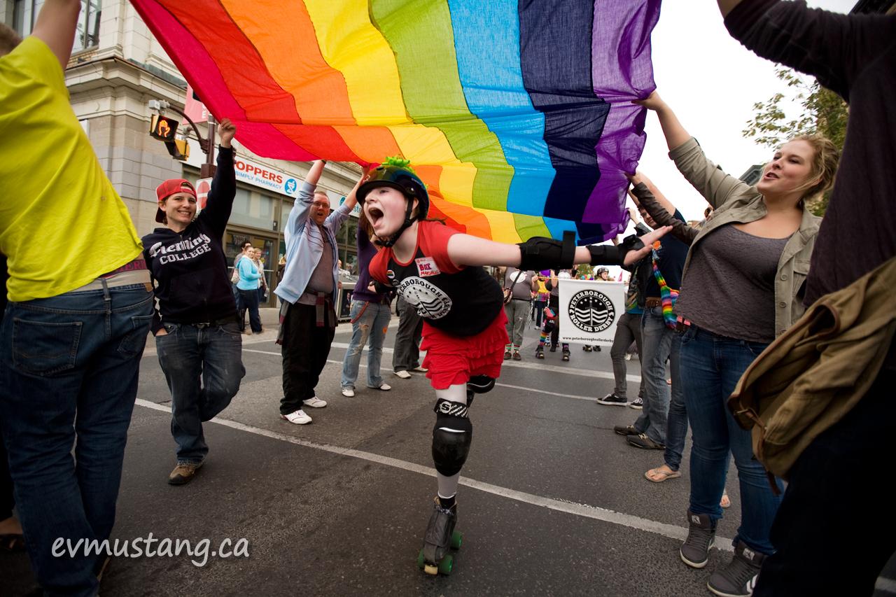 image of peterborough roller derby skater under kenner collegiate rainbow flag