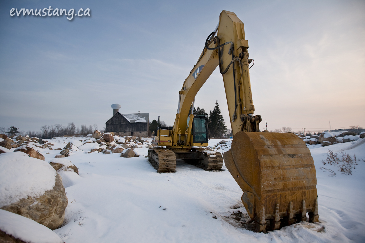 image of power shovel with barn in snow