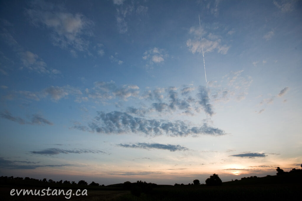 image of vapour trail through clouds in a sunset sky